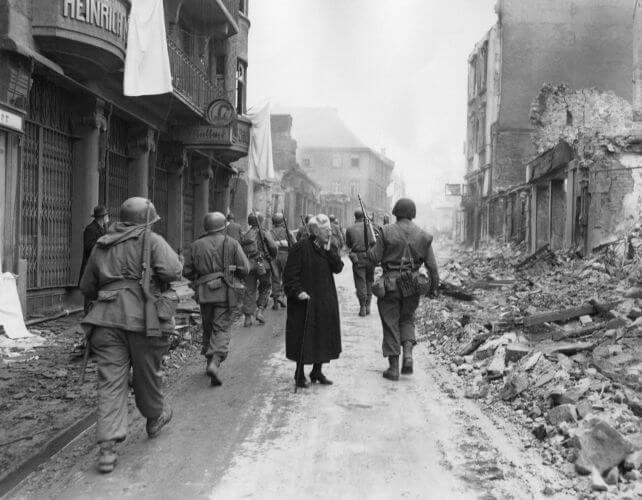 Tropas aliadas marchando sobre uma cidade alemã em ruínas ao final da Segunda Guerra.*