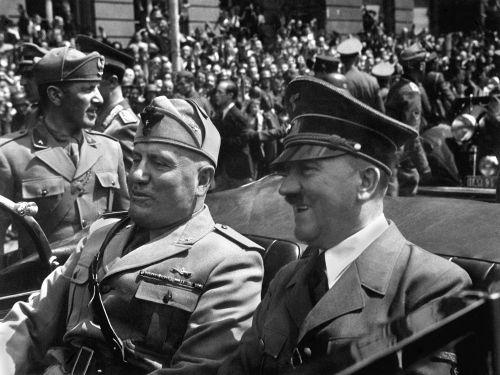 Acima, Benito Mussolini (à esquerda) desfilando em carro aberto ao lado de Adolf Hitler