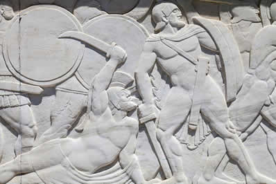 Escultura em pedra retratando uma batalha realizada por espartanos
