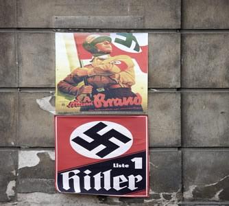 Cartaz de propaganda nazista. É possível perceber a referência a Hitler e a simbologia militarista
